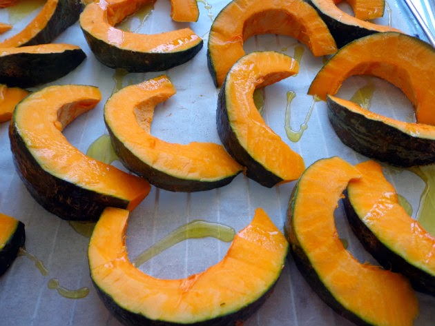 Kabocha slices on a baking sheet lined with parchment paper