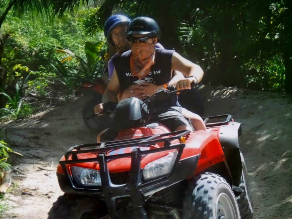 Photo of my wife and I on an ATV in a thick jungle-looking area.