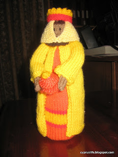 the orange and yellow-garbed wise man in the knitted nativity scene