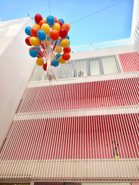 A mass of multicolored balloons float several stories above the photographer
