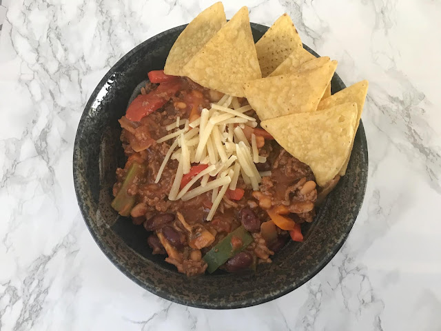 bowl of chilli with tortilla crisps on side and grated cheese on top