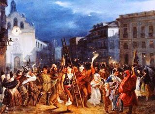 Un numerso grupo de personas con gorros y disfarces pasa por la antigua Puerta del Sol bailando y bebiendo, excepto uno de ellos, con traje regional, que transporta una escalera.