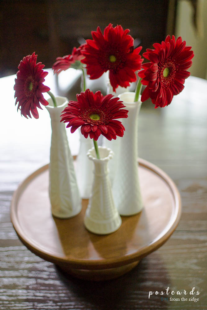 centerpiece with red zinnias in vintage milk glass vases