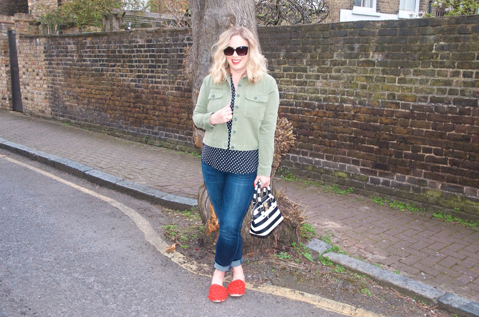 Green jacket, polka dot top, jeans, striped bag, red shoes