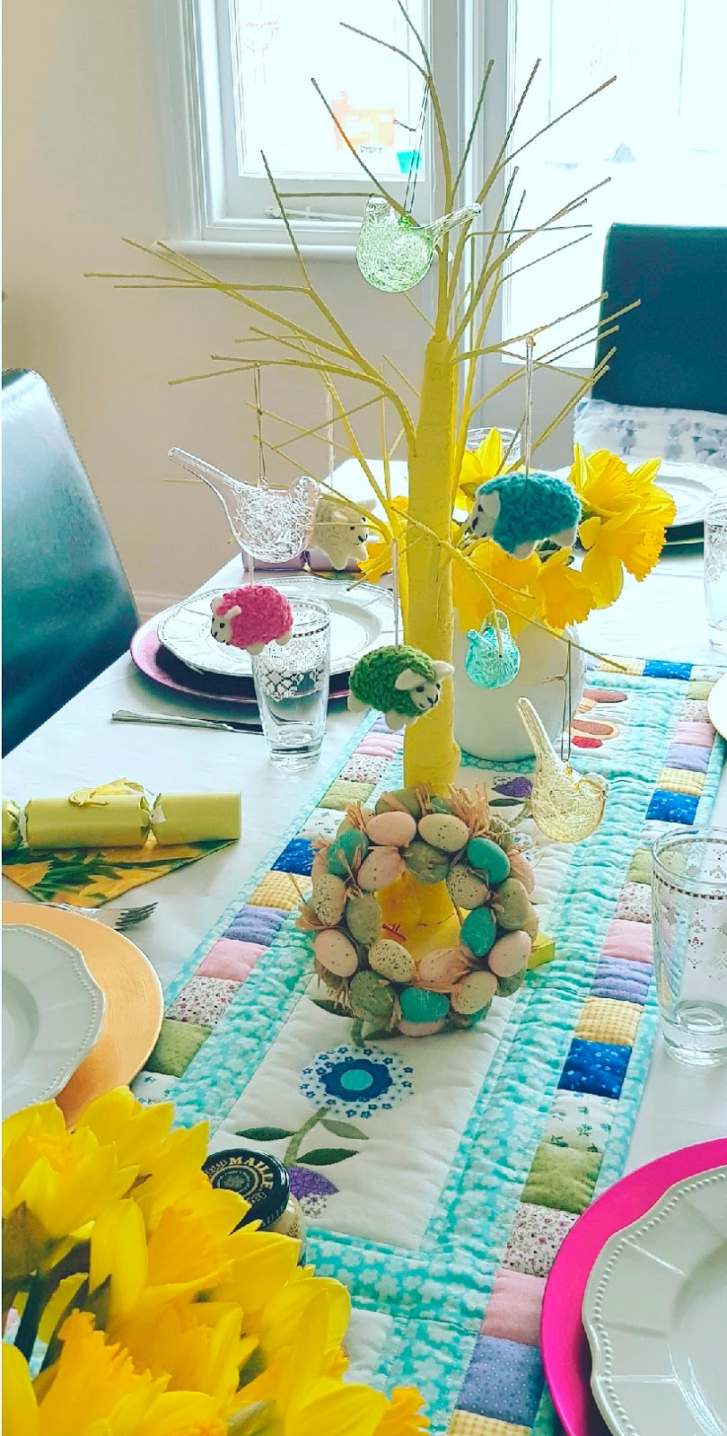 A table decorated for Easter in London, UK, April 2018. Includes an Easter wreath and an Easter tree decorated with glass birds and woolly sheep.