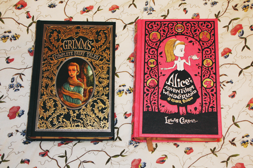 the cover of a leatherbound copy of grimm's fairytales, next to the cover of a leatherbound copy of Alice's adventures in wonderland, on a duvet on a bed