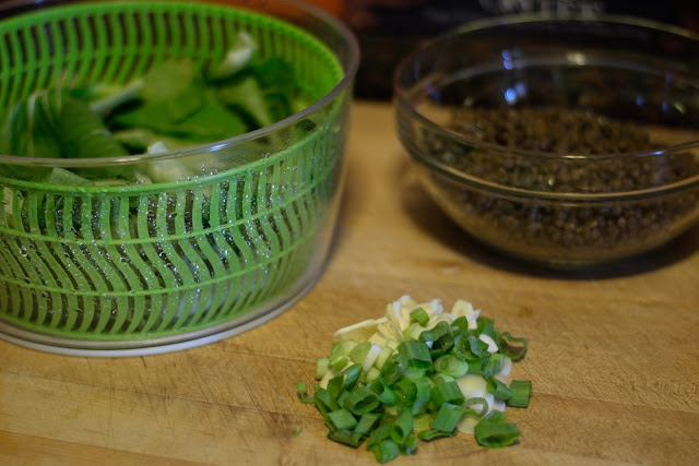 The prepared bok choy, lentils, green onions, and garlic on a cutting board.