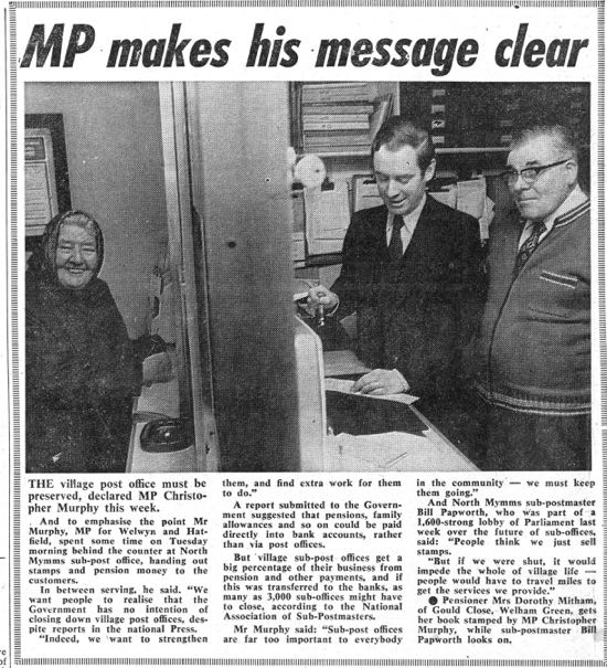 Scan of Newspaper cutting of a staged photo-opportunity involving MP Christopher Murphy (centre), Dorothy Mitcham (left), and sub-postmaster, Bill Papworth (right). Cutting from the Peter Miller Collection