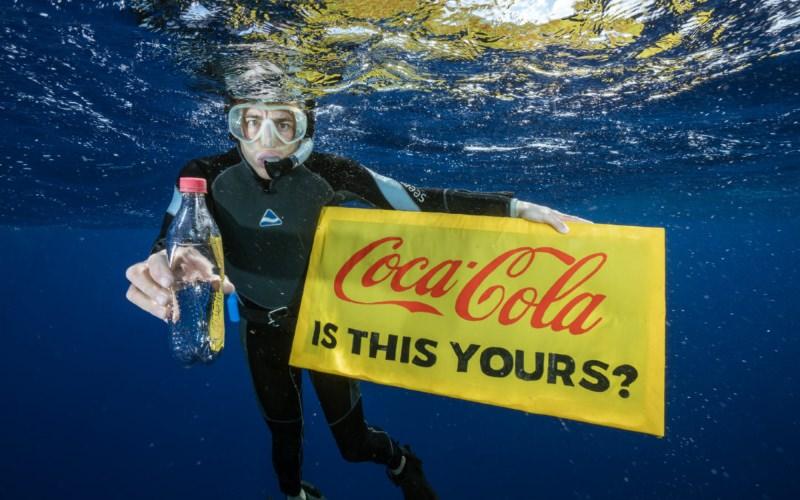 Mergulhador com garrafa da Coca-Cola