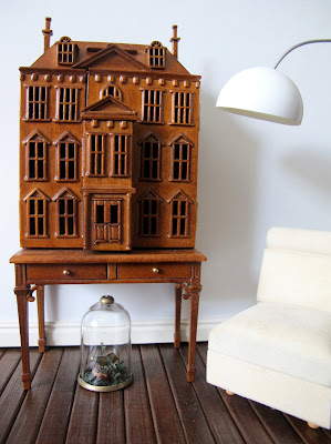 Modern dolls' house miniature scene with a wooden dolls' house mounted on a desk next to a white slipper chair, an arc lamp and with a cloche on the floor underneath it.