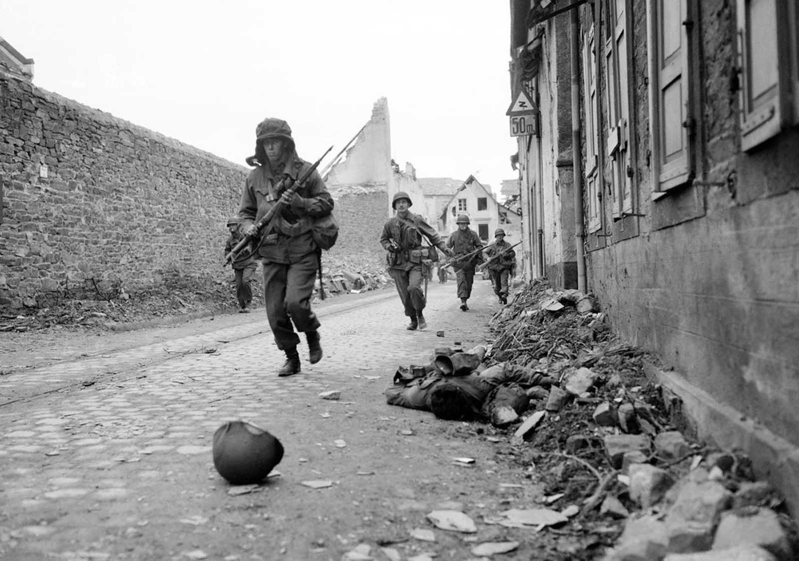 Soldiers of the 3rd U.S. Army storm into Coblenz, Germany, as a dead comrade lies against the wall, on March 18, 1945.