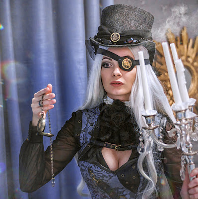 Woman in steampunk clothing (black and blue) with a top hat and eyepatch. Steamgoth style