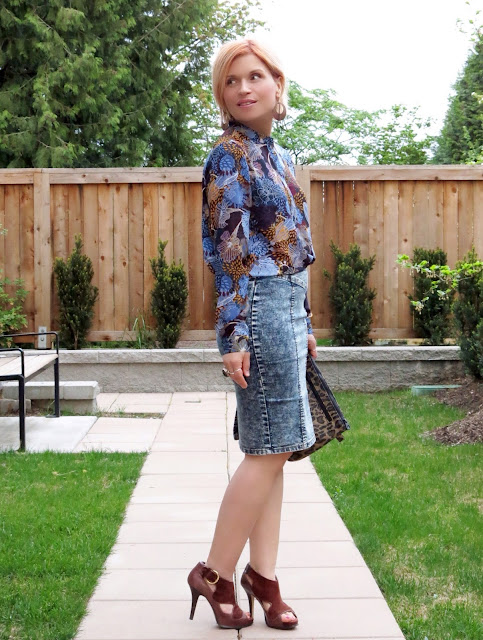 styling an acid-washed denim pencil skirt with a floral blouse, leopard-print clutch, and suede platform heels