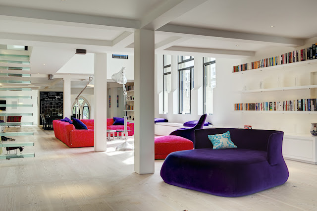 Picture of open living room with pink couch and purple chair