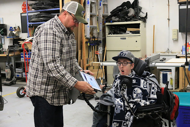 Clay attaches an iPad to modular hose, fixed to Bryson's wheelchair