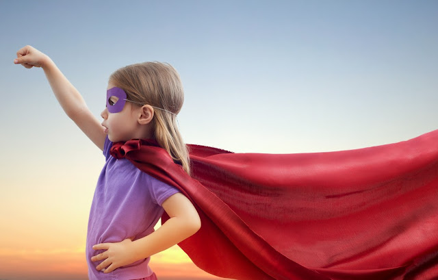 Little girl wearing superhero red cape and eye mask