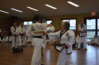 An adult taekwondo martial arts woman breaking a board