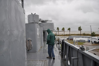 Man walking on deck of Navy ship in rain