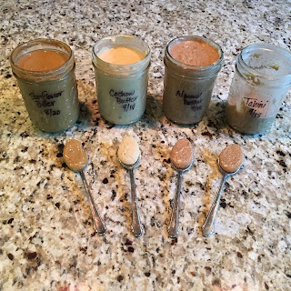 Photo of four pint jars and four spoonfuls of homemade nut and seed butters: Roasted Sunflower, Raw Cashew, Raw Almond, and Raw Sesame Tahini. https://trimazing.com/