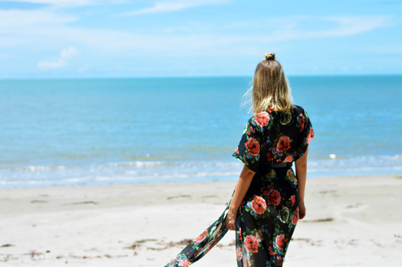 girl with blonde lob looking out to sea on tropical beach port douglas