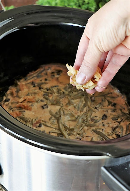 Sprinkling French's Fried Onions on Top of Green Bean Casserole in a Crock Pot Image