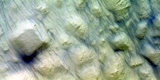 The Colour and Stereo Surface Imaging System, CaSSIS, onboard the joint ESA-Roscosmos ExoMars Trace Gas Orbiter imaged the Ariadne Colles region at 34ºS on 2 September 2018.  The image shows an unusual terrain type – sometimes referred to as chaotic blocks – but what is particularly striking are the large number of dark streaks. One possible interpretation is that these features were produced during the recent dust storm: they could have resulted from dust devils stirring up the surface dust. Credit: ESA/Roscosmos/CaSSIS, CC BY-SA 3.0 IGO