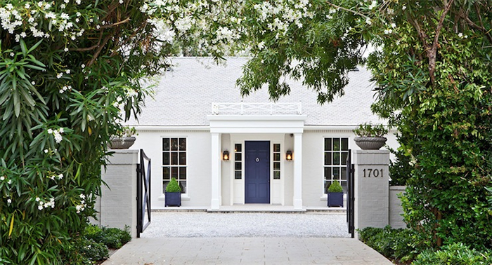 Gwyneth Paltrow's white brick house with navy front door and topiaries flanking the entry.