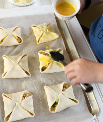 Little Dude brushing hand pies with egg yolk wash and topping with cheese