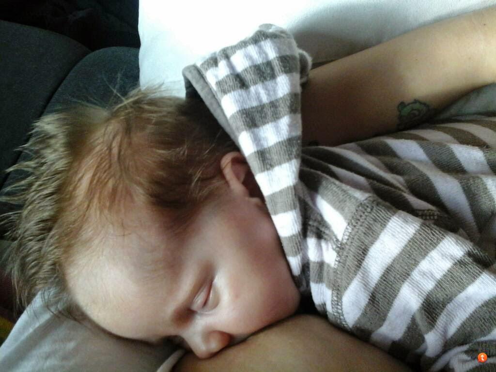 Baby stillt an mütterlicher Brust