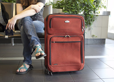 Photo of young woman traveler with suitcase