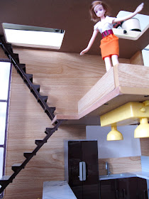 A doll looking over the mezanine railing of the modern Lori Loft to Love dolls' house.