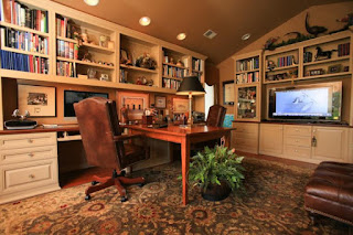 An image of beautiful living room with Tv,study desk and bookshelves above it