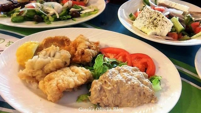 Na talerzy tradycyjne greckie danie smażony dorsz, pasta czosnkowa i pokrojone pomidory.