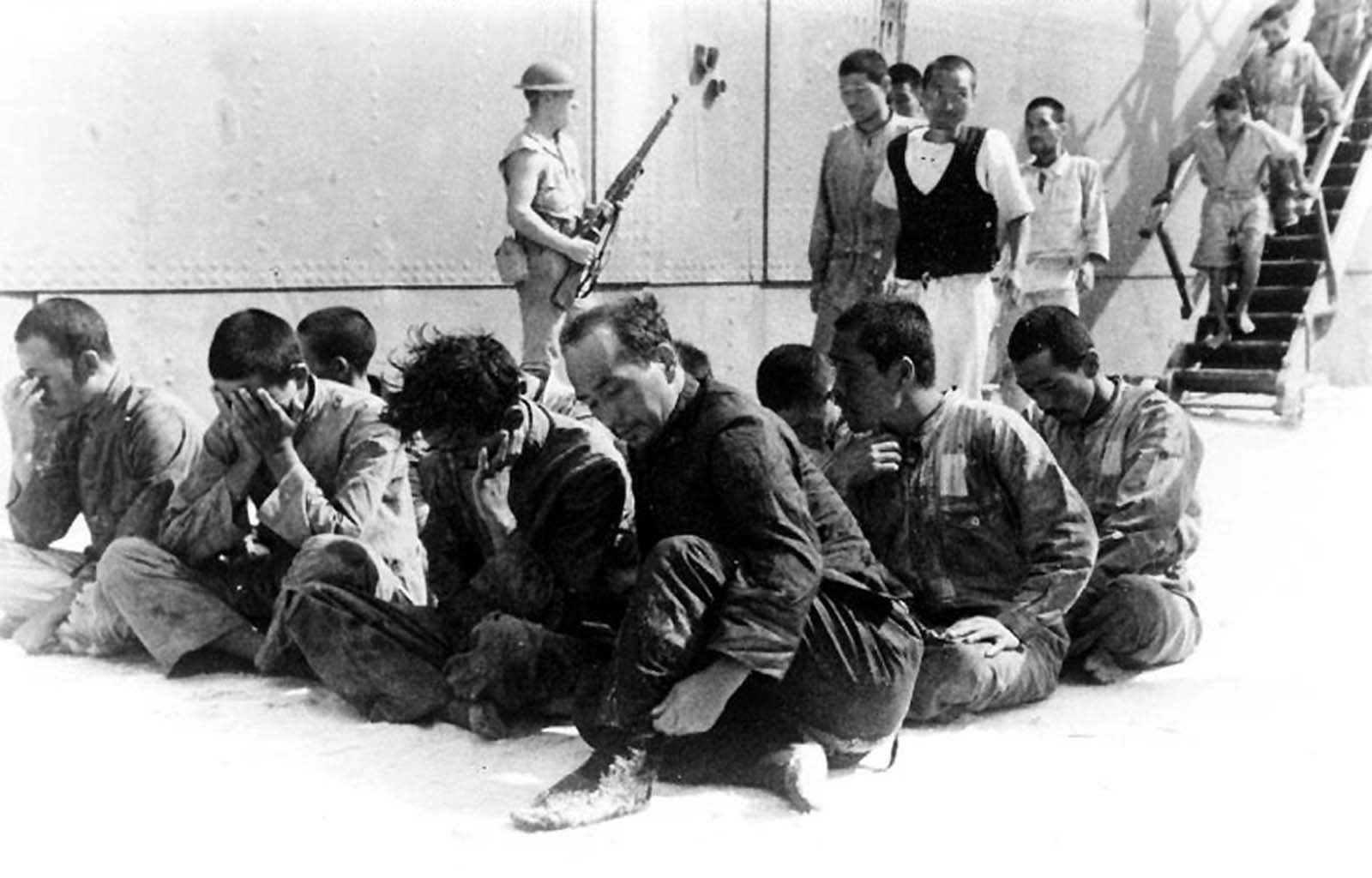 Japanese prisoners of war under guard on Midway, following their rescue from an open lifeboat by USS Ballard, on June 19, 1942. They were survivors of the sunken aircraft carrier Hiryu. After being held for a few days on Midway, they were sent on to Pearl Harbor on June 23, aboard USS Sirius.