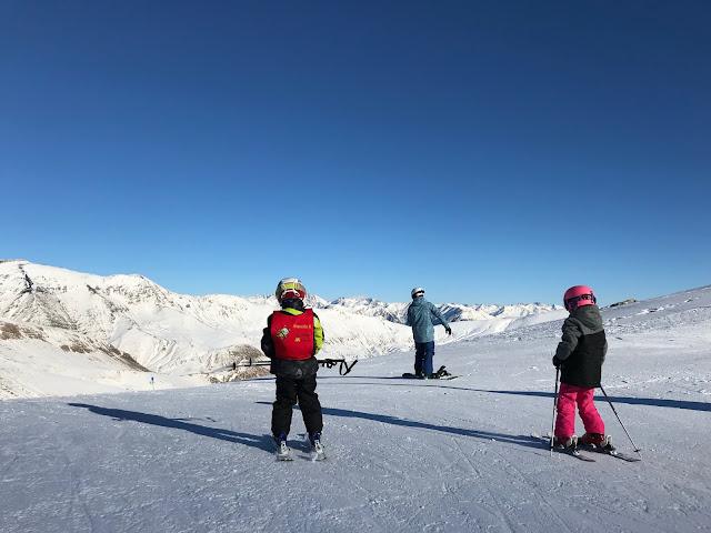Niños esquiando junto a su padre