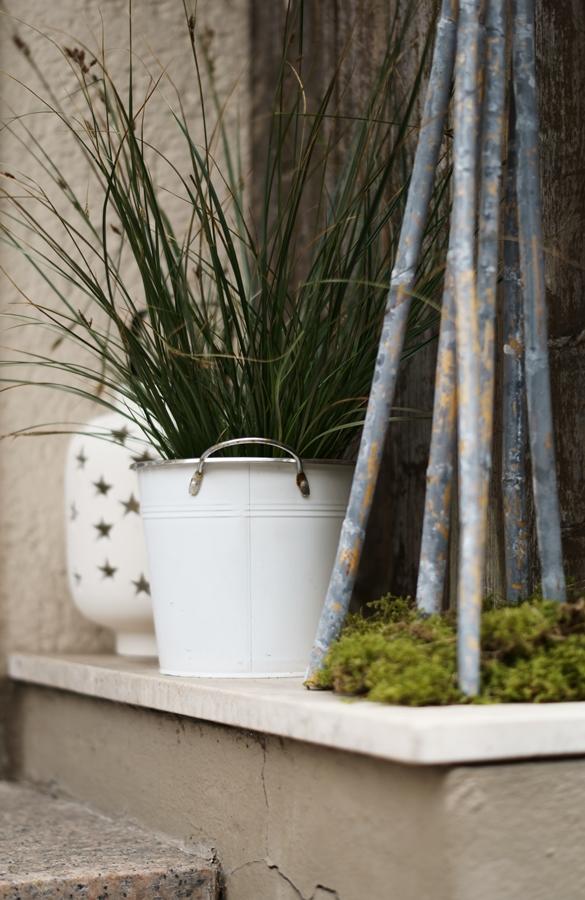 Blog + Fotografie by it's me! - Hauseingang im Februar - Gras in weißem Übertopf vor einer Holzwand