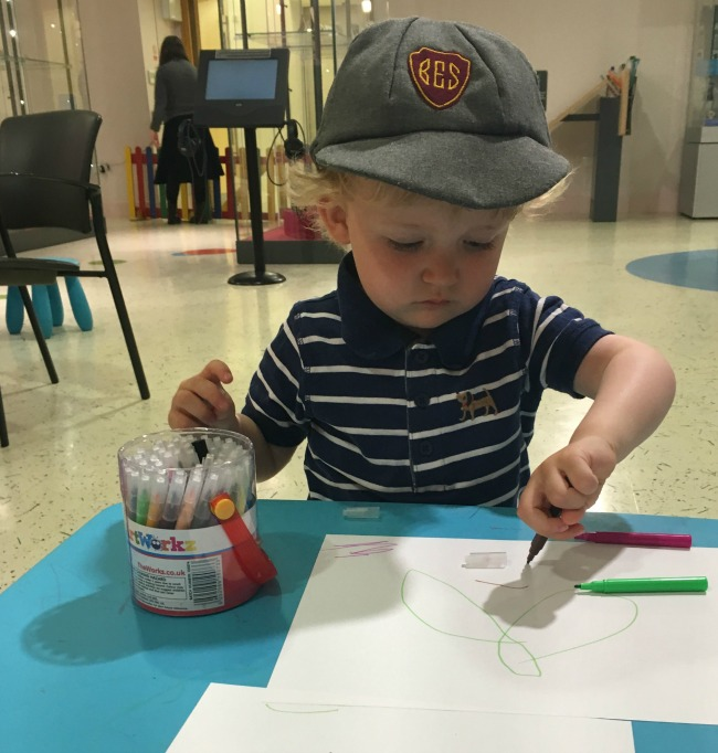 our-week-of-plays-toddler-wearing-cap-and-drawing-at-Cardiff-story-museum