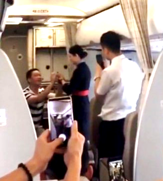 In a clip shared by Pear Video, a male passenger on a flight from Xi An to Yinchuan is shown getting up from one knee after successfully proposing to his girlfriend, who happens to be a stewardess on the flight.