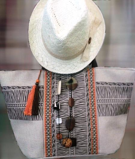 Bolso con franja estampado étnico, sombrero de paja y collar a juego.