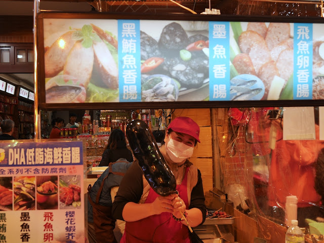 woman holding a large fake Cuttlefish Sausage