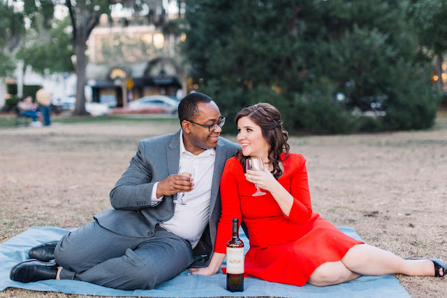 engaged couple drinking wine picnic in the park
