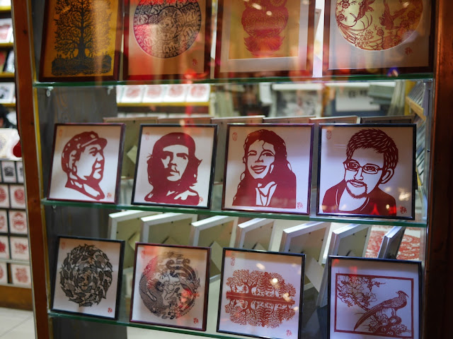 red paper-cut portraits of Mao Zedong, Che Guevara, Michael Jackson, and Edward Snowden