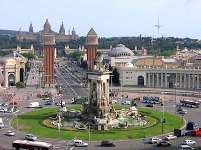 Vista panorámica de la Plaza España, con la fuente, las Torres venecianas y el recinto ferial de fondo