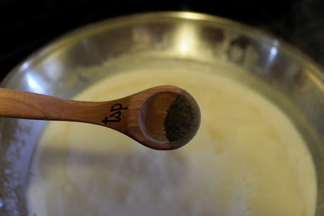 A picture of a measuring spoon over a bowl with black pepper in it.
