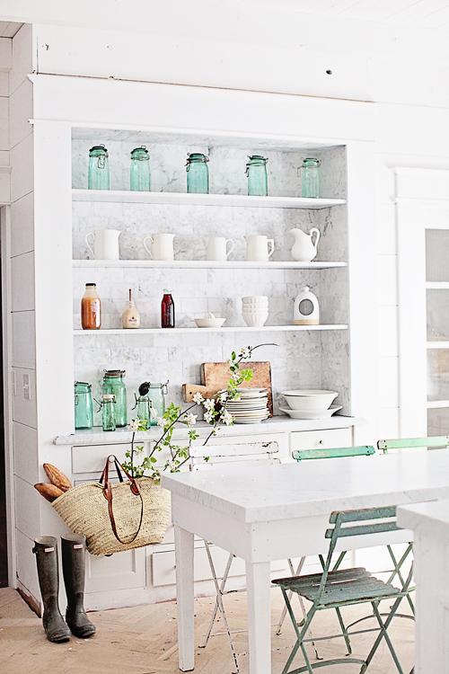 Farmhouse style kitchen with white shelves and market basket. Dreamy Whites.