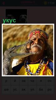 небольшой крокодил пытается укусить мужчину за лицо