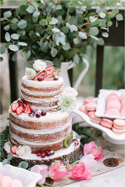 naked wedding cake with eucalyptus backdrop