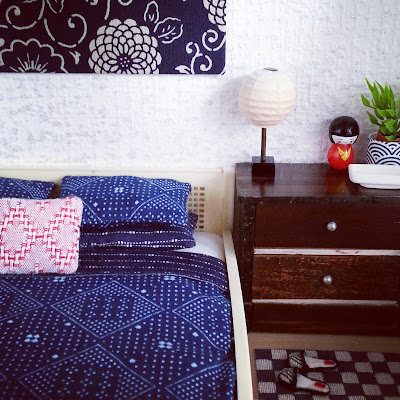 Corner of a one-twelfth scale Japanese-themed bedroom with a cream cane bed with blue-and-white bedding, a chest of drawers with a rice-paper lamp. a kokeshi dolls, a plant in a blue-and-white Japanese pot and a white rectangular bowl displayed on it and, on the floor, a blue and white checked rug with a pair of embroidered slippers on it.