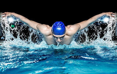 a swimmer races toward the finish line with the butterfly stroke