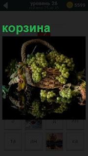 На гладкой поверхности стола стоит корзина с виноградными гроздьями и отражается на поверхности